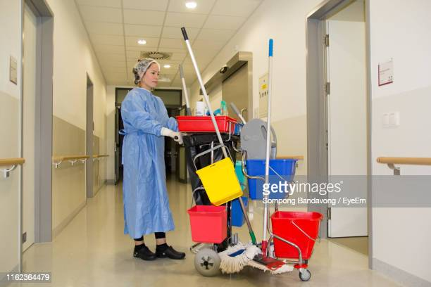 full length of female cleaner working at corridor in hospital - cleaner stock pictures, royalty-free photos & images