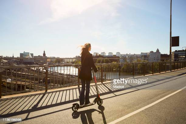 full length of female commuter riding electric push scooter on bridge in city against sky - scandinavia stock pictures, royalty-free photos & images