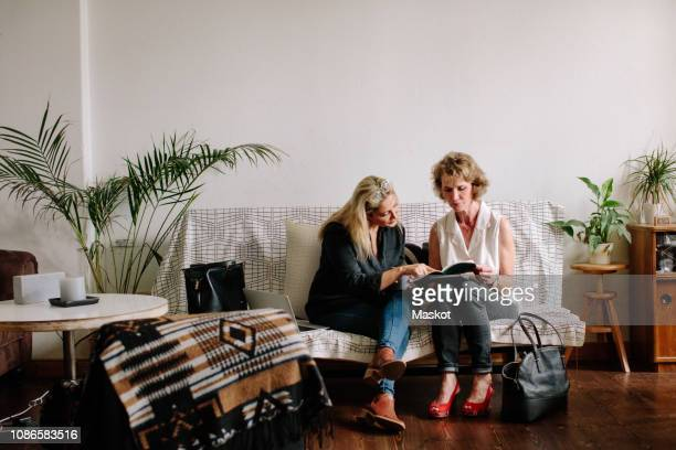 full length of female design professionals discussing while sitting on sofa against wall at home office - nur erwachsene stock-fotos und bilder
