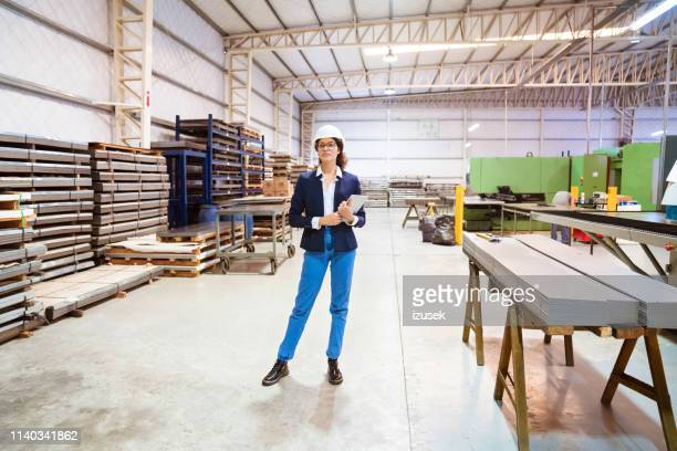 full length of female manager standing in factory - full length stock pictures, royalty-free photos & images