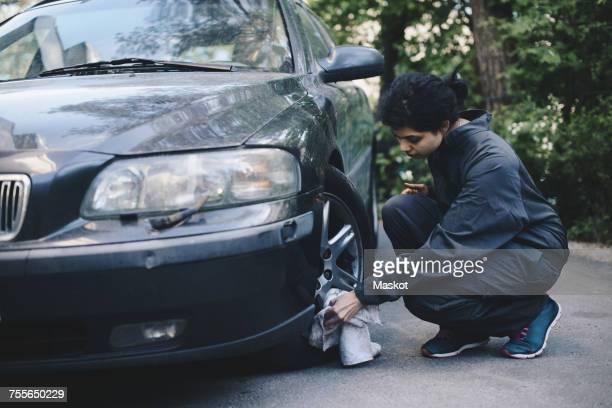 Full length of female mechanic cleaning car wheel outside auto repair shop