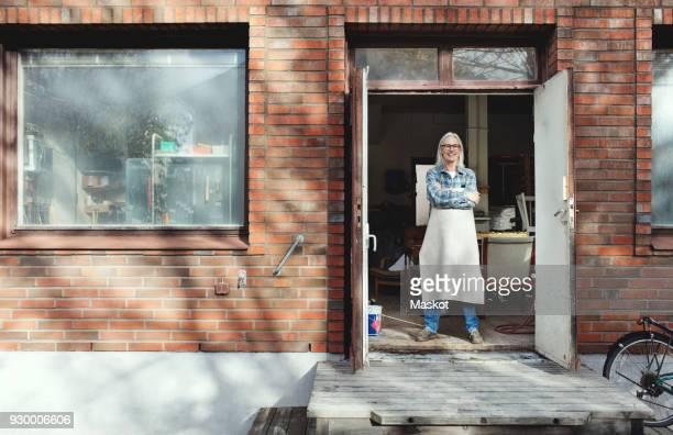 Full length of female owner standing at entrance of workshop