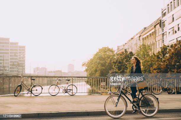 full length of female professional riding bicycle on road in city against sky - radfahren stock-fotos und bilder