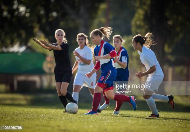 full length of female soccer players in action during the match. - referee stock pictures, royalty-free photos & images