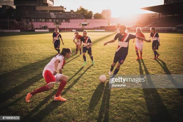 volledige lengte van vrouwelijke voetballers in actie op een wedstrijd bij zonsondergang. - damesvoetbal stockfoto's en -beelden