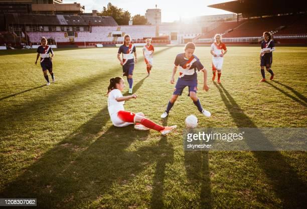 duración completa de las jugadoras de fútbol femeninos en acción en un partido. - fútbol femenino fotografías e imágenes de stock