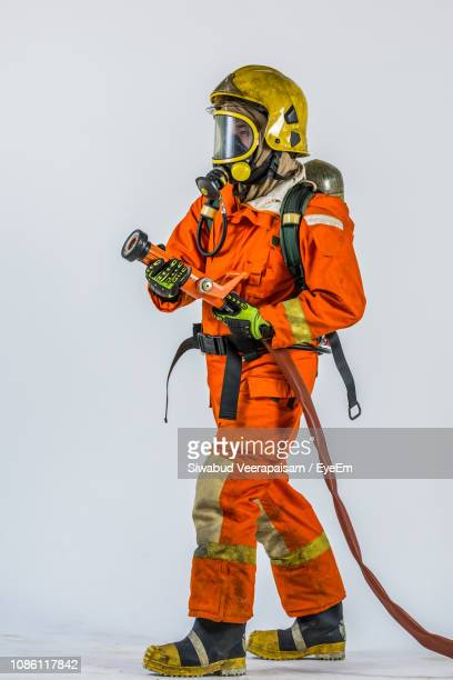 full length of firefighter holding fire hose against white background - fire protection suit stock pictures, royalty-free photos & images