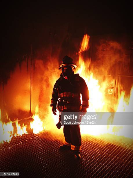 full length of firefighter standing near fire - fire protection suit stock photos and pictures