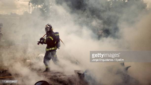 full length of firefighter walking amidst smoke - firefighter stock pictures, royalty-free photos & images