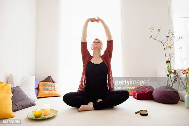 Full length of fit woman sitting with arms raised at home