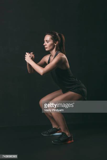 full length of focused woman doing squat exercise against black background - hurken stockfoto's en -beelden