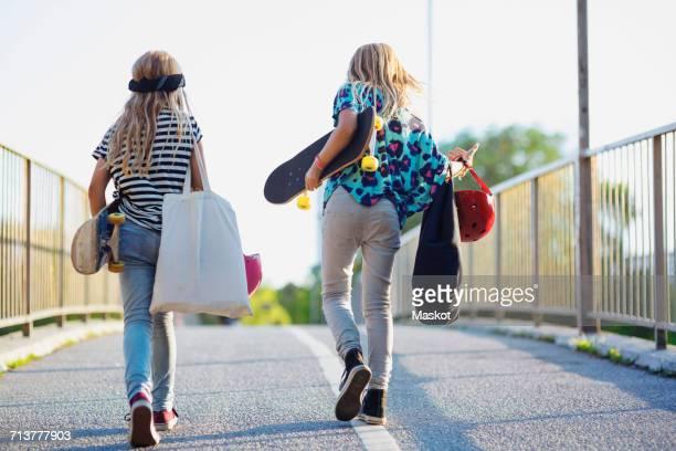 Full length of friends carrying skateboard while walking on bridge