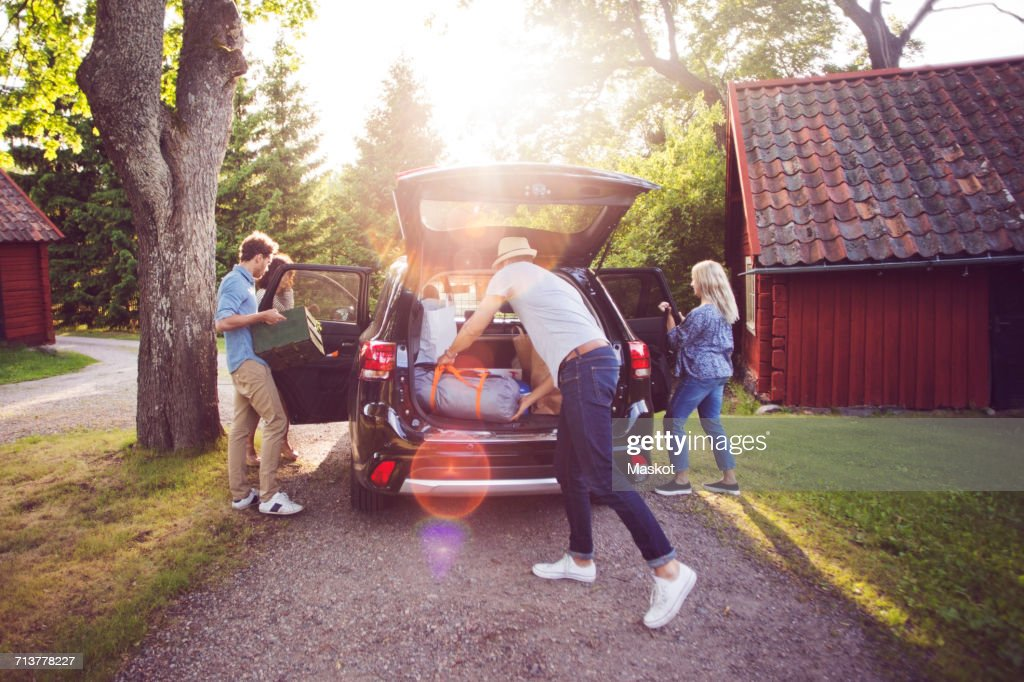 Full length of friends loading luggage into car on road during sunny day : Stock Photo