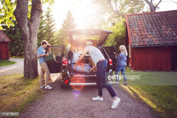 Full length of friends loading luggage into car on road during sunny day