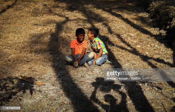 full length of friends sitting on land - amdad hossain stock pictures, royalty-free photos & images