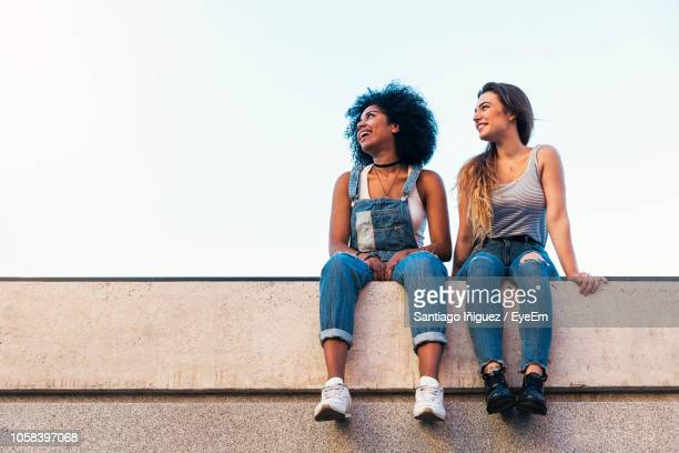 full length of friends sitting on retaining wall against clear sky - retaining wall stock pictures, royalty-free photos & images