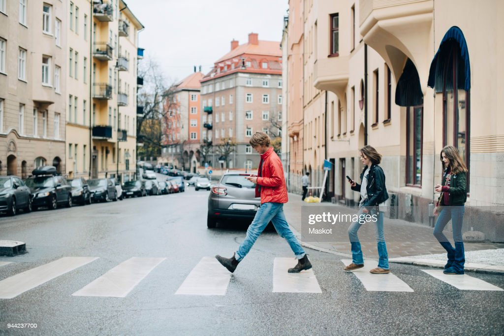 Full length of friends using mobile phone while crossing street in city : Stock Photo