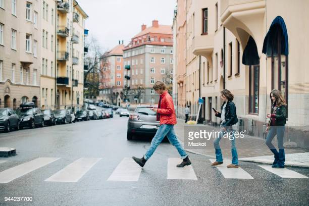 full length of friends using mobile phone while crossing street in city - pedestrian crossing stock photos and pictures