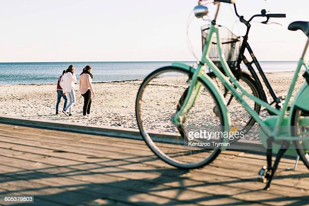 Full length of friends walking on beach with bicycles in foreground