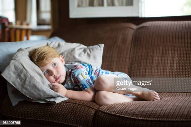 full length of frightened boy lying on sofa at home - terrified stock pictures, royalty-free photos & images