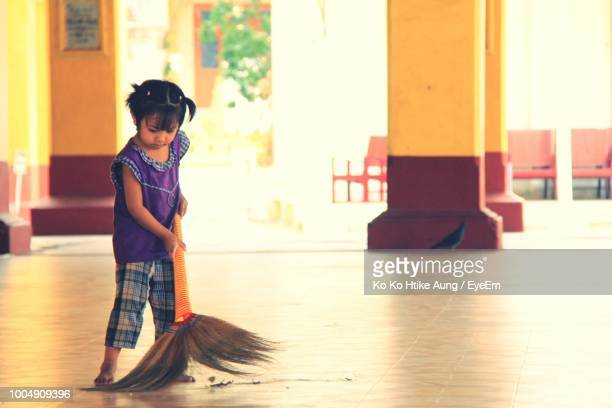 full length of girl cleaning floor with broom - sweeping stock pictures, royalty-free photos & images