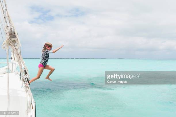 full length of girl diving in sea from boat against cloudy sky - turks and caicos islands stock pictures, royalty-free photos & images