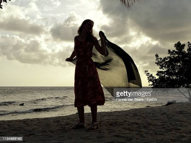 Full Length Of Girl Holding Textile While Standing At Beach Against Sky