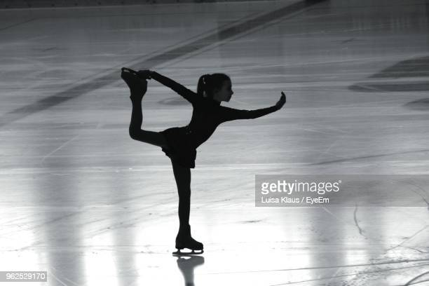 full length of girl ice-skating on rink - ice skating stock pictures, royalty-free photos & images