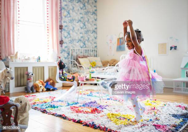 full length of girl in fairy costume dancing at home - mask dance stock pictures, royalty-free photos & images
