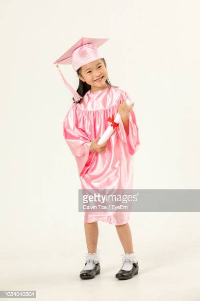 full length of girl in pink graduation gown against white background - graduation background stock pictures, royalty-free photos & images
