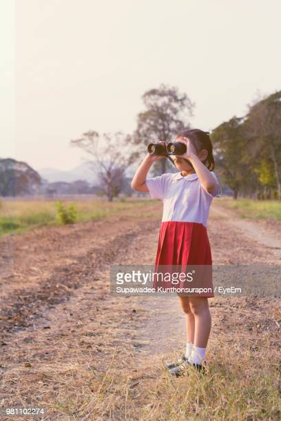full length of girl in school uniform looking through binoculars while standing at field - very young thai girls stock photos and pictures