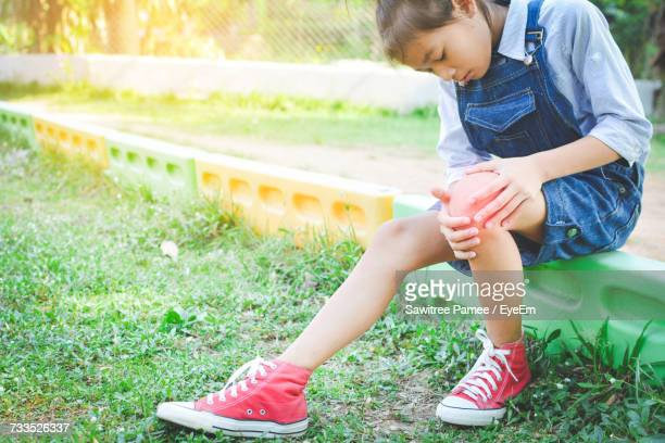 Full Length Of Girl Looking At Knee While Sitting On Field