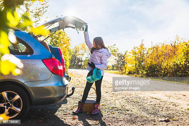 Full length of girl looking into open car trunk in countryside