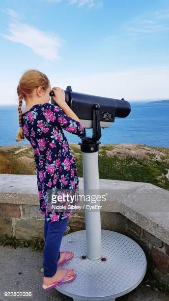 full length of girl looking through coin-operated binoculars while standing against sea - sibley stock photos and pictures