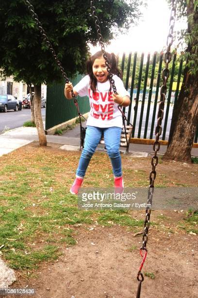 Full Length Of Girl Playing On Swing In Playground