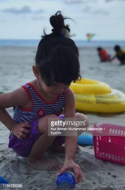Full Length Of Girl Playing With Toys On Sand At Beach