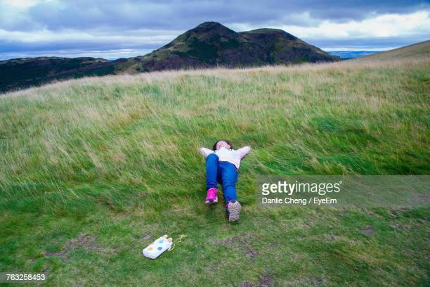 Full Length Of Girl Relaxing On Grassy Field Against Cloudy Sky