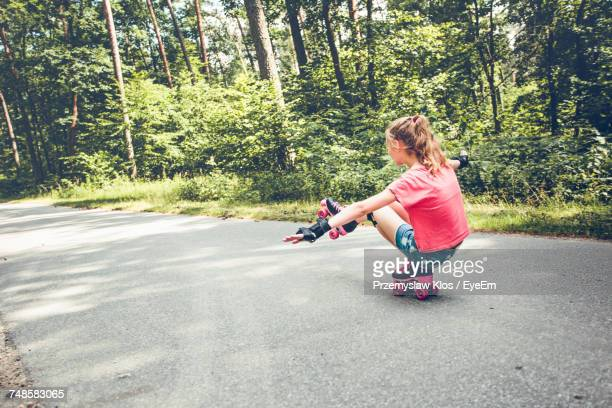 Full Length Of Girl Roller Skating By Trees On Road At Forest