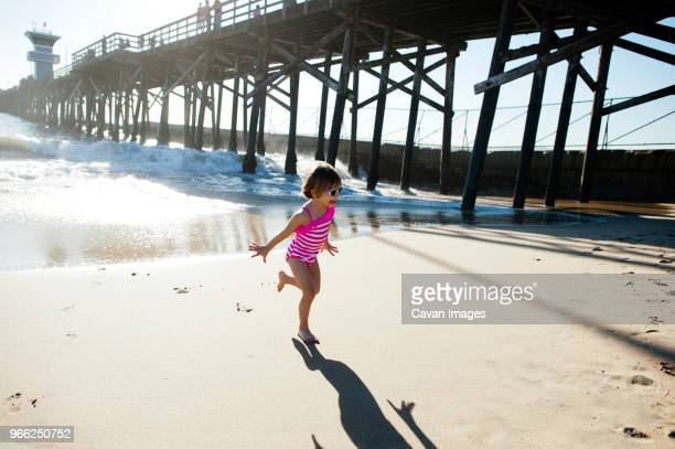 full length of girl running on shore at seal beach - seal beach stock pictures, royalty-free photos & images