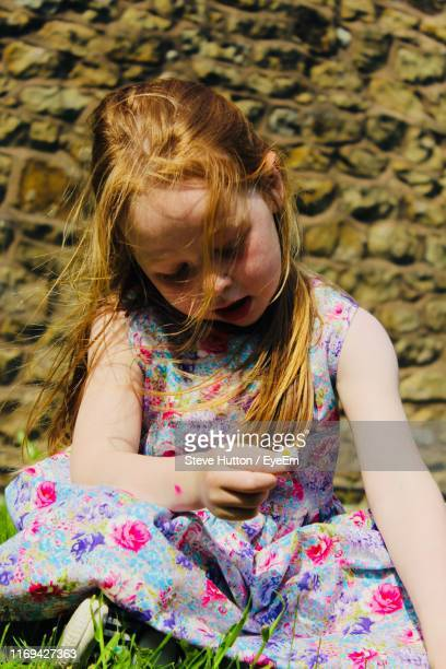 full length of girl sitting against wall - hutton stock photos and pictures