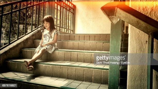 Full Length Of Girl Sitting On Steps