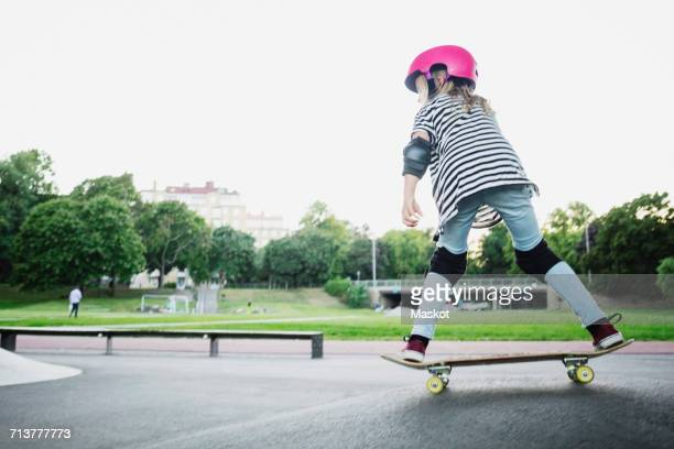 full length of girl skateboarding at park against clear sky - padding stock photos and pictures