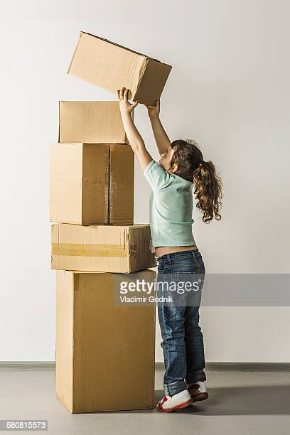 Full length of girl stacking boxes in house