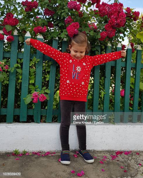 full length of girl standing against flowering plants - elena knouzi stock pictures, royalty-free photos & images