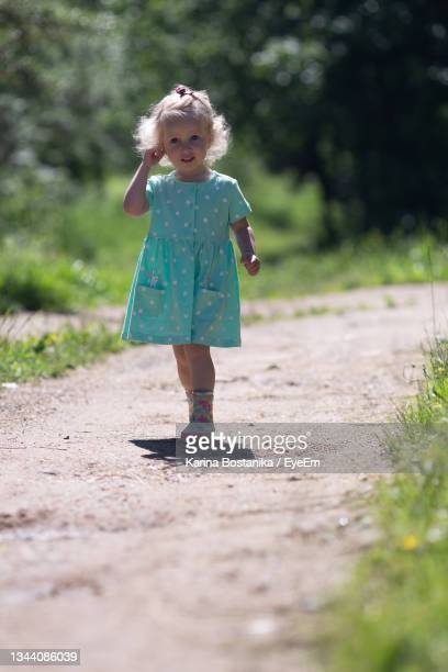 full length of girl standing against plants - rubber dress stock pictures, royalty-free photos & images