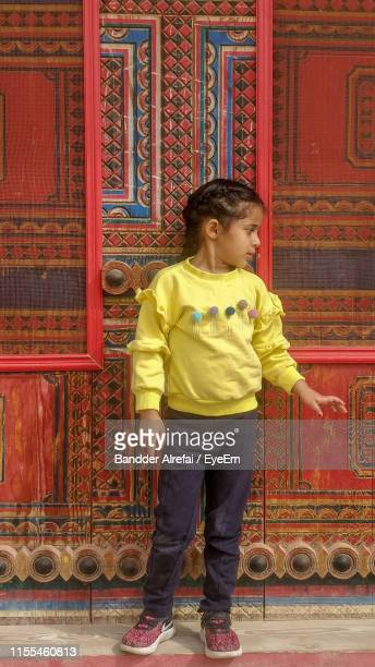 full length of girl standing against wall - saudi arabia stock photos and pictures
