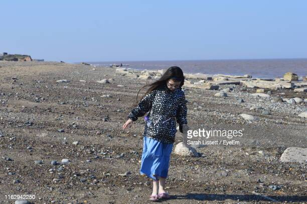 full length of girl standing at beach against clear sky - sarah sands stock pictures, royalty-free photos & images