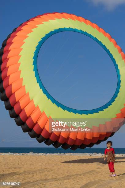 full length of girl standing by colorful large ring kite at beach - shaifulzamri foto e immagini stock