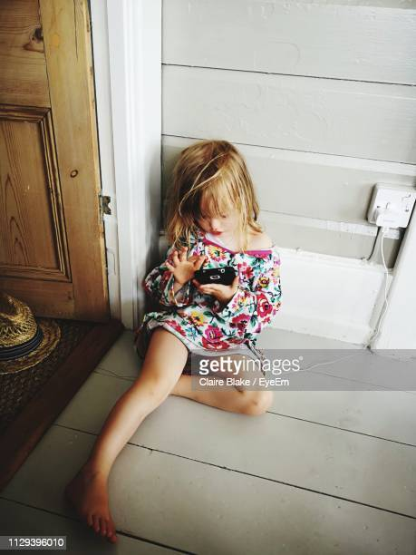 full length of girl using mobile phone at doorway - claire castel bildbanksfoton och bilder