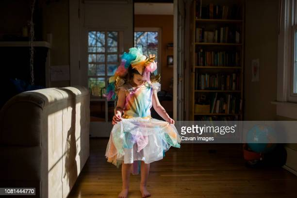 full length of girl wearing colorful unicorn costume standing on hardwood floor at home - multi colored dress stock pictures, royalty-free photos & images
